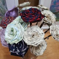 Tie, music sheet and map roses on stems